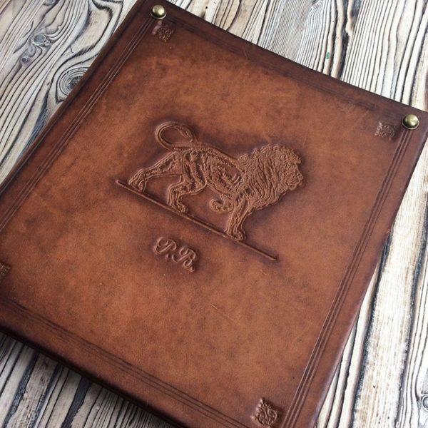 Кожаный альбом для монет с львом и инициалами на обложке.