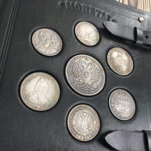 Папка для монет с монетами на обложке из натуральной кожи.